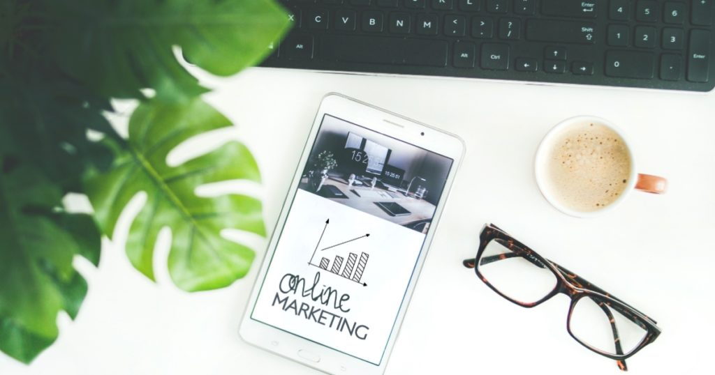 Online Marketing - Desk with phone, pair of glasses, coffee and a plant next to keyboard